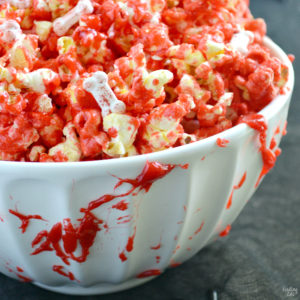 Learn how to make bloody popcorn with bones including directions for adding edible fake blood to your serving dishes! Halloween popcorn has never been so fun and it makes a great snack to serve Halloween party guests!