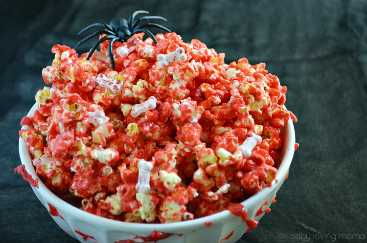 Learn how to make bloody popcorn with bones for Halloween, including directions for adding edible fake blood to your serving dishes! Perfect treat for Halloween parties!