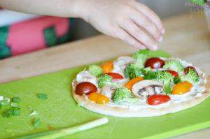 Adding Green Onion to Veggie Flatbread Appetizer