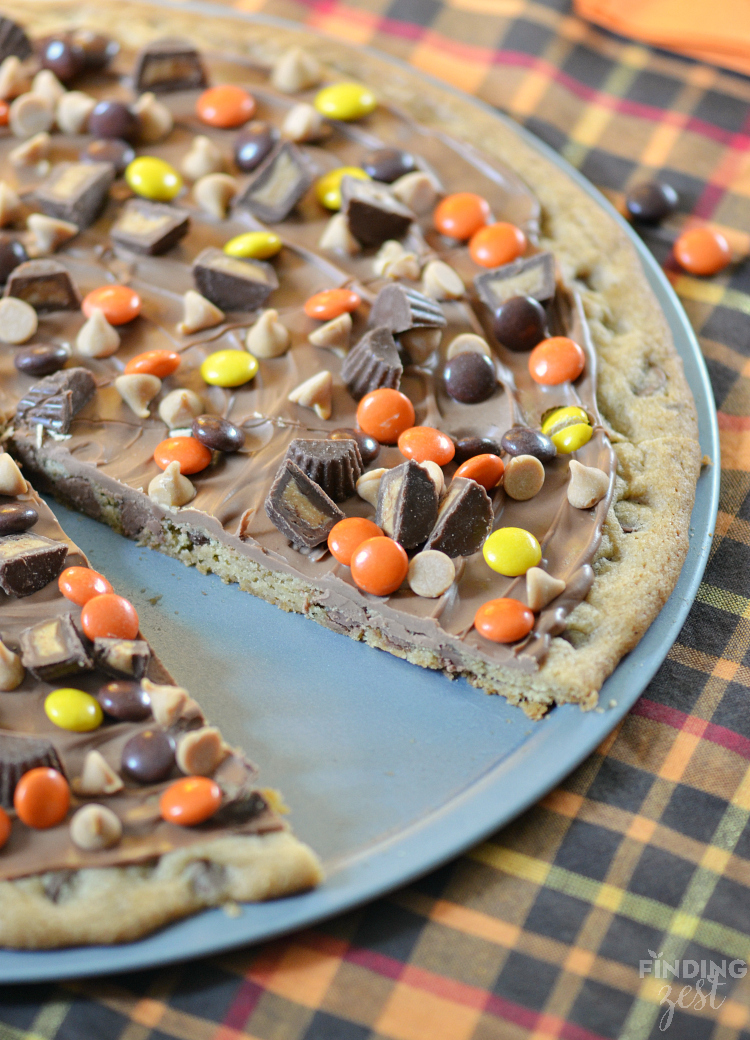 This peanut butter chocolate chip cookie pizza features a chewy chocolate chip cookie base and is covered in peanut butter candies and chocolate! It is sure to impress a crowd! Perfect for a Halloween party or to use up leftover Halloween candy.