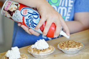 Adding Whipped Cream to Mini Pumpkin Pies