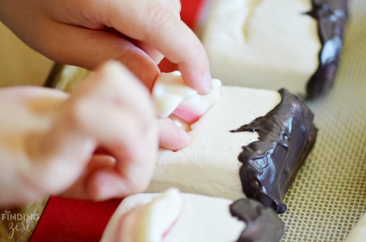Inserting Gummy Fangs into Vampire Marshmallows