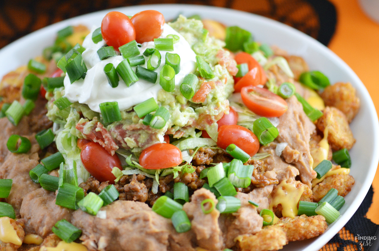 This Loaded Totchos recipe will win the crowd on game day! Perfect for March Madness, these potato rounds are covered in queso dip, refried beans and guacamole!