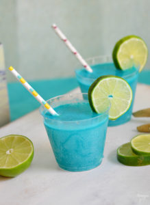 Throwing an mermaid, pool or ocean themed party? This Mermaid Punch recipe is quick and delicious featuring tropical flavors! Your guests will love this blue pina colada punch!
