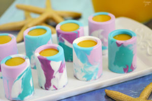 Surprise birthday party guests with these Mermaid Smoothie Shots! These marbled chocolate shot glasses are perfect for filling with your favorite tropical fruit smoothies. These kid friendly shots work great for any Under the Sea themed party!