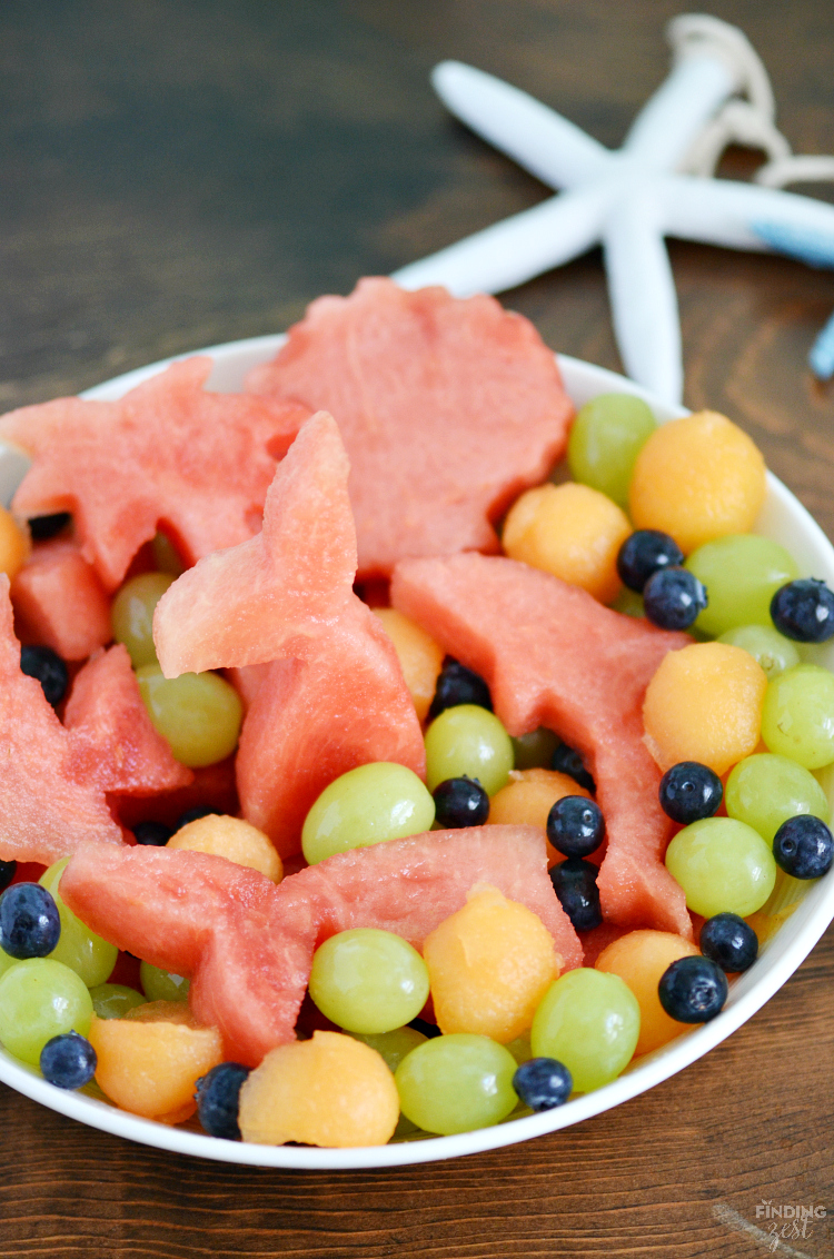 On the hunt for ocean or mermaid party ideas? This Under the Sea Mermaid Honey Lime Fruit Salad is a healthy birthday party food with watermelon cutouts! This kid friendly snack also works well for any brunch, summer cookout or pool party!