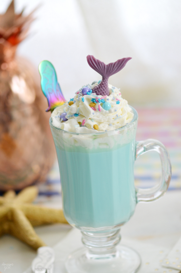 Make a cup of cocoa extraordinary with this Blue Mermaid Hot Chocolate recipe You have to try it! Using homemade white hot chocolate, this delicious blue drink is loaded with fun sprinkles, whipped cream and topped with a chocolate mermaid tail. Mermaid lovers of all ages will go nuts for this hot mermaid drink! Perfect to serve guests at a mermaid birthday party. The mermaid spoons also make great party favors.
