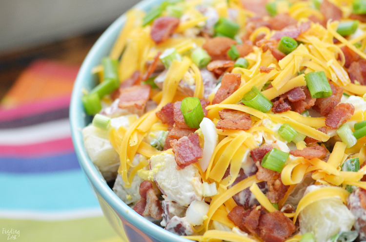 This red potato salad with bacon is loaded with flavor and perfect for your next potluck or picnic. This loaded potato salad recipe includes all your favorite baked potato fixings including sour cream, cheese and green onion but also contains a surprise ingredient in the dressing!
