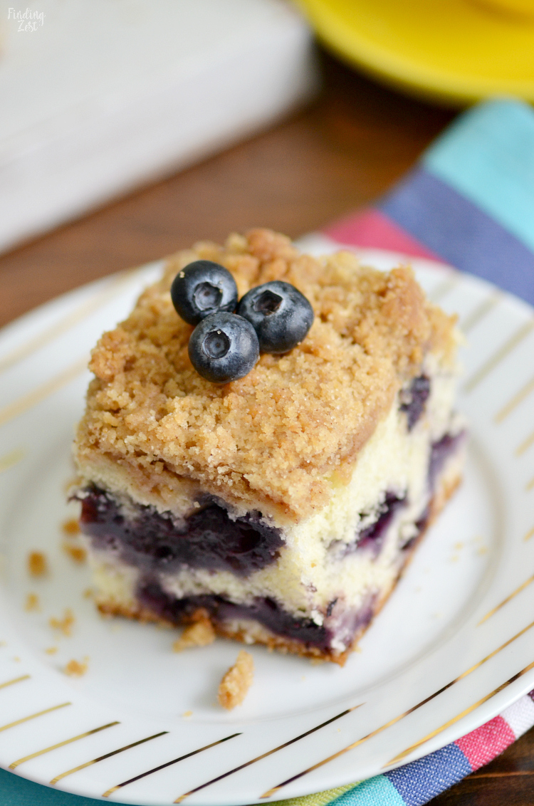 You are going to love this blueberry buckle recipe, bursting with fresh blueberries! This blueberry coffee cake has a crunchy streusel topping and can be served any time of day, including breakfast. Made in 9x13 inch pan, this blueberry buckle recipe feeds a crowd.