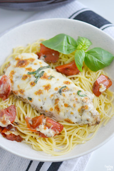 This baked caprese chicken recipe is an easy weeknight meal with melted mozzarella that no one can resist! All you need is 15 minutes to get this smothered chicken with tomatoes in the oven. Serve over pasta for a simple meal solution.