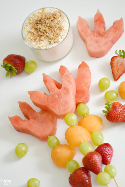 Celebrate the back to school season with this easy dinosaur snack idea with dinosaur footprints! Kids will love these fun dino fruit skewers with yogurt fruit dip inspired by We Don't Eat Our Classmates, a humorous children's book by Ryan T Higgins.