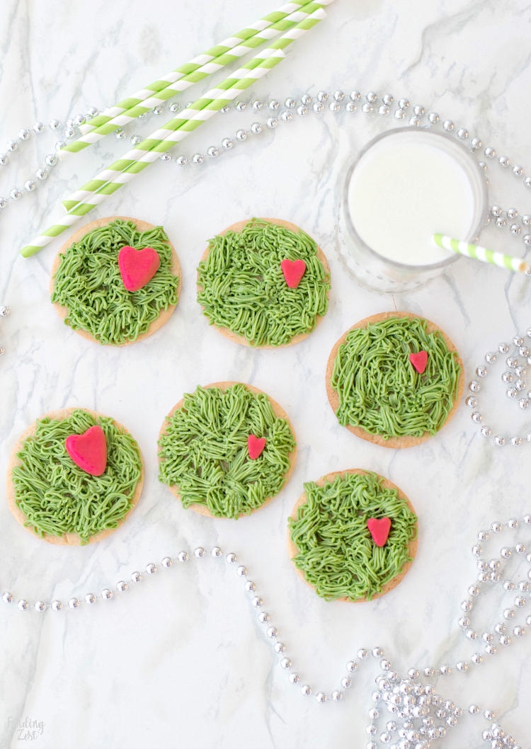 Everyone will love these adorable Grinch Cookies to celebrate the beloved Dr. Seuss character during the holiday season! This sugar cookie features green frosting to look like fur and three sizes of fondant hearts to represent his heart growing three sizes that one fateful day. These Grinch-inspired treats are super easy and fun for all ages to make and enjoy!