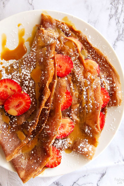 Surprise your family or special someone with these chocolate crepes made from scratch! This easy crepe recipe is a perfect dessert featuring chocolate, strawberries  and caramel sauce for a combination that is nothing short of heavenly! Try it for a delicious Valentine's Day dessert or your next birthday or anniversary celebration.