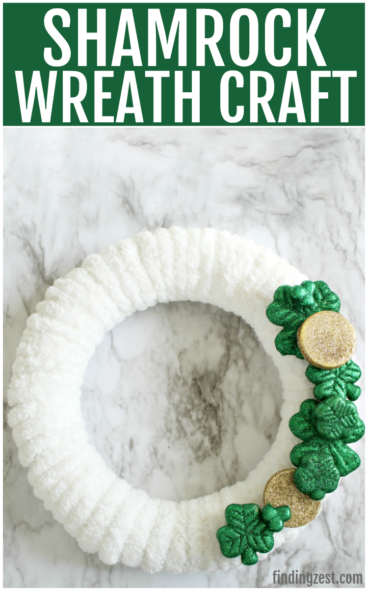 Make your own St. Patrick's Day decorations with this easy DIY shamrock wreath! This yarn wreath features fluffy white yarn along with glitter shamrock and gold coin embellishments that can be purchased from the dollar store. You'll love this quick and inexpensive shamrock wreath craft for St. Patrick's Day!