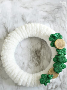 white yarn wreath with glitter shamrocks and gold coins