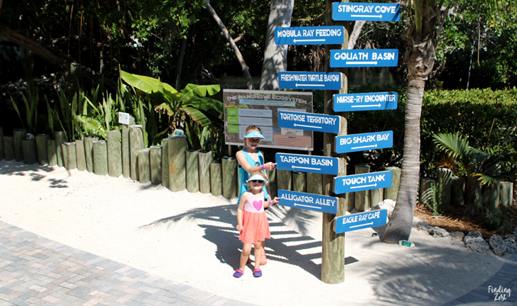 Girls pointing at entry signs at Aquarium Encounters Florida Keys