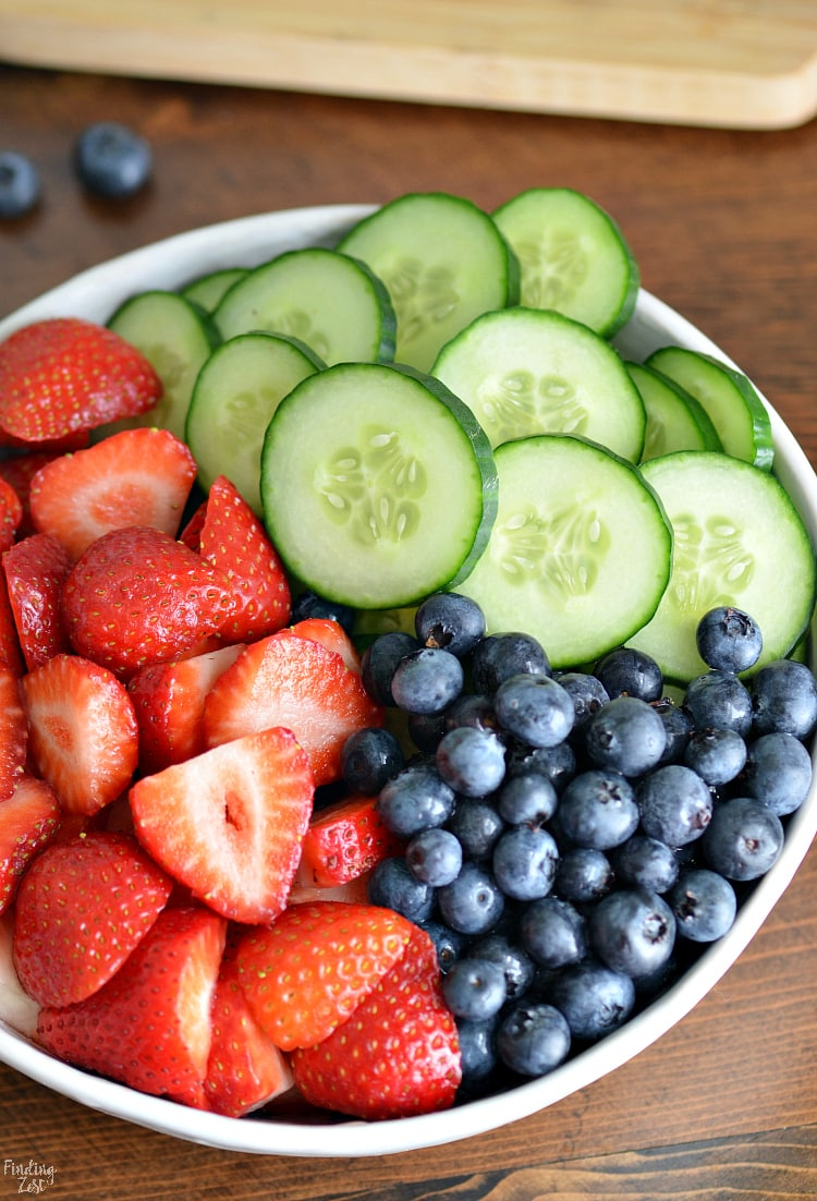 Fresh summer salad with sliced strawberries, cucumbers and blueberries in a bowl