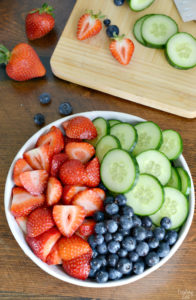 Ingredients for strawberry cucumber salad in a bowl.
