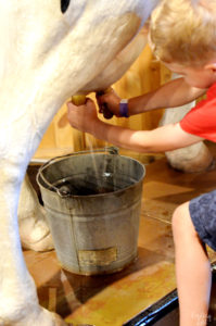 Pretending to milk a cow at Phelps Youth Pavilion