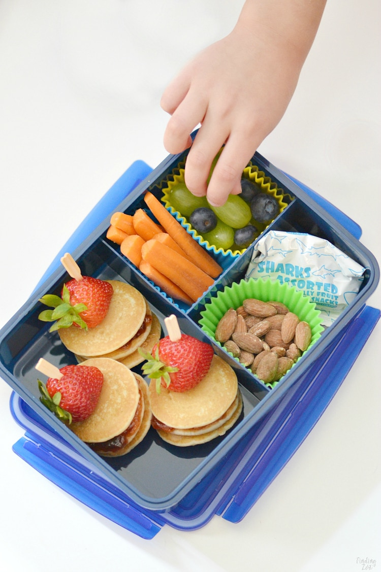 Child reaching for Mini PB&J Pancake Stacks in a School Lunchbox.