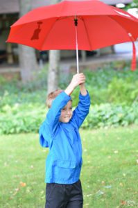 Playing with red umbrella outside