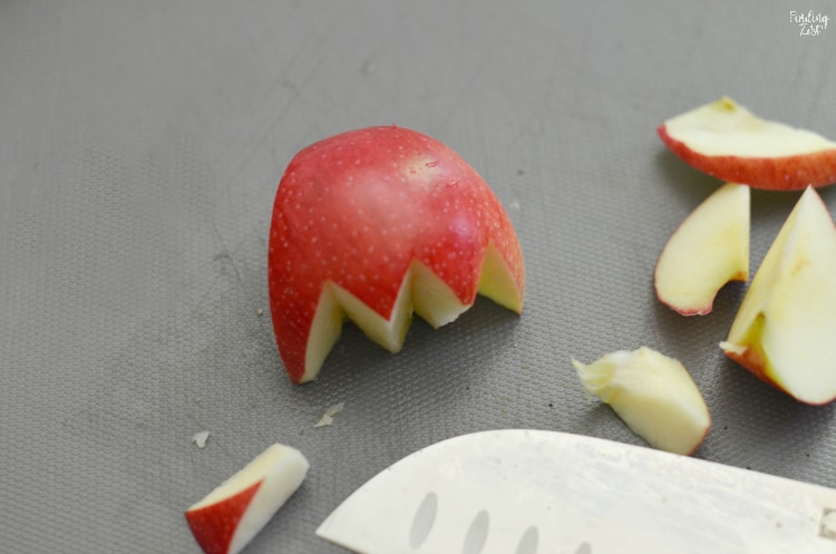 Cutting a red apple to resemble an umbrella