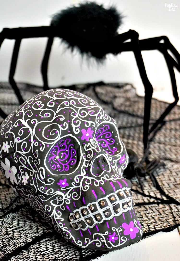 Learn how to make sugar skull decor with a dollar store plastic skull and chalkboard paint!