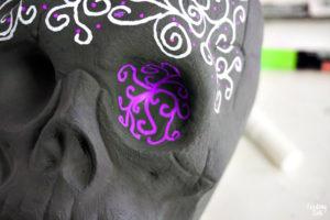 Purple swirl design in eye sockets on black skull craft