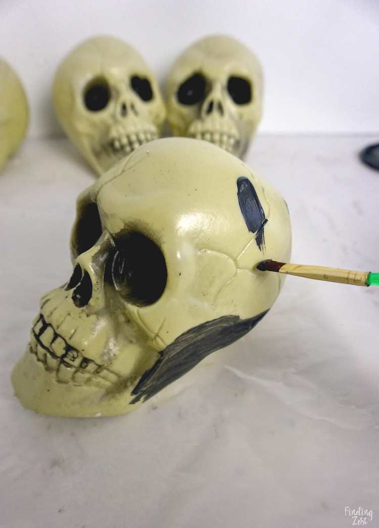 Painting plastic skull with chalkboard paint for Halloween decor.