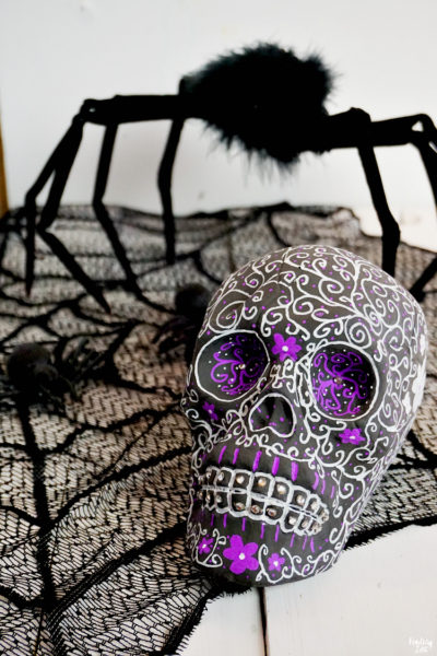 Use chalkboard paint to create these eye-catching sugar skulls for Halloween. This dollar store skull is transformed with minimal supplies into a beautiful design with small flowers, swirls and dots. Give this easy Halloween craft a try, even if you only have limited artistic talent!