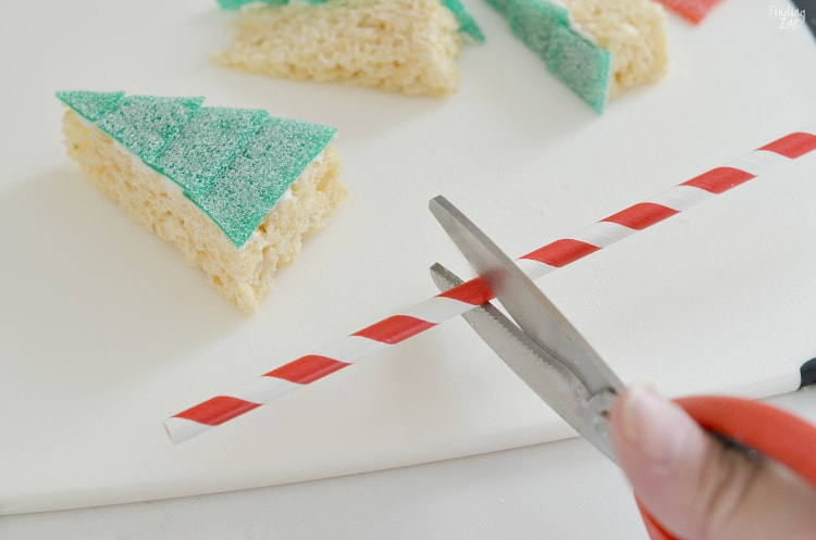 cutting red and white straw to put in bottom of edible christmas tree