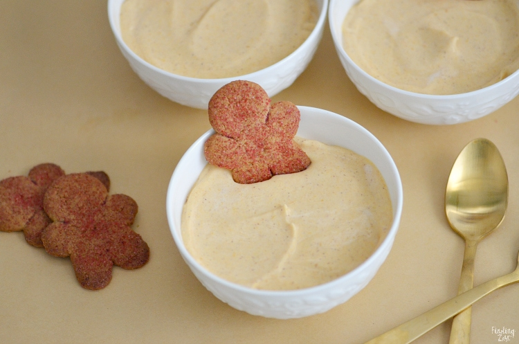 Pumpkin pudding in a small bowl with a gingerbread man cookie