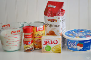 Ingredients needed for pumpkin pudding including pudding, whipped topping, milk, cinnamon and gingerbread cookies