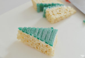 Rice Krispie Treats topped with sour candy cut into a triangle