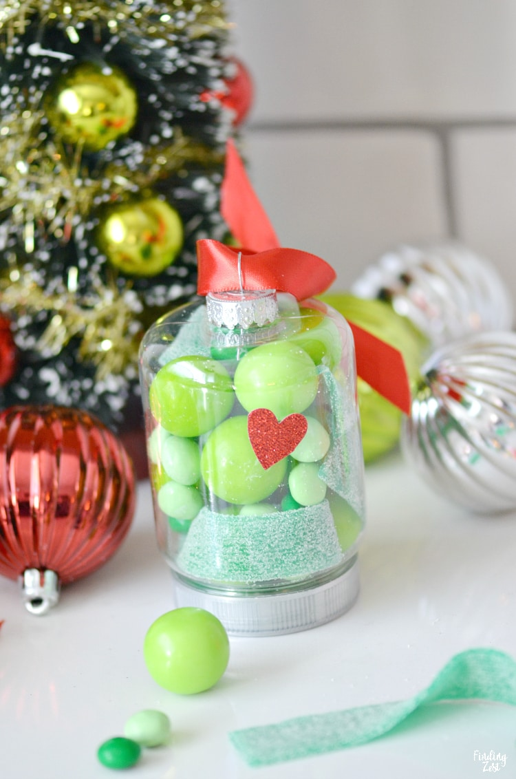 DIY Grinch ornament with red ribbon, heart and plastic oranment