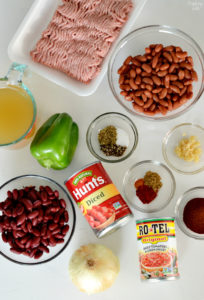 Turkey chili ingredients in bowls including ground turkey, broth, canned tomatoes, spices, onion, kidney beans, garlic