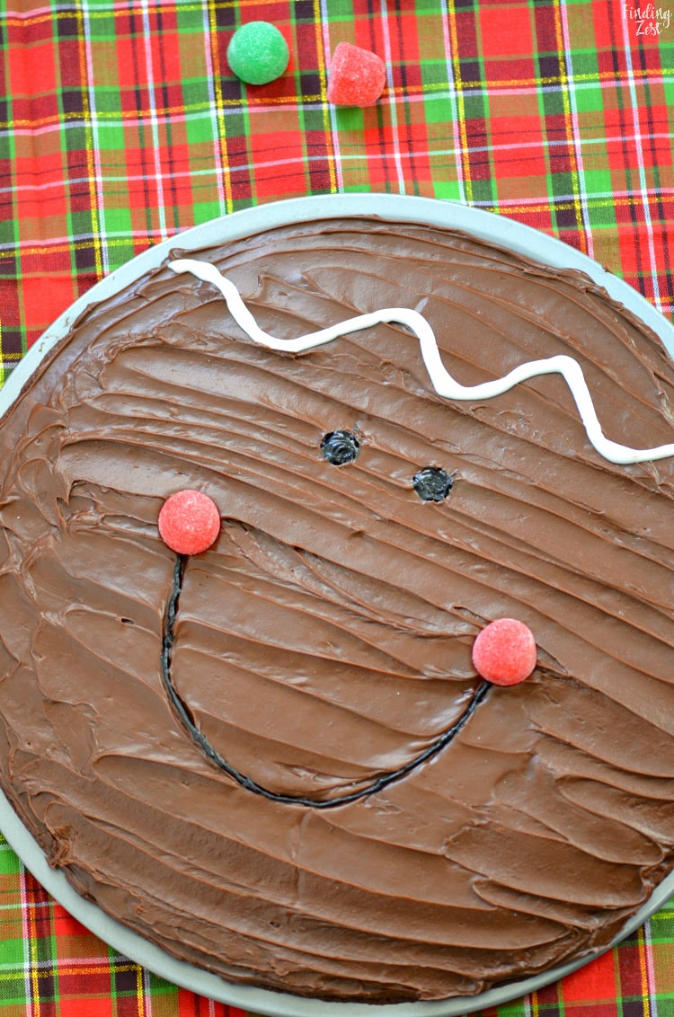 Using candy and icing to make a smiling gingerbread face on a brownie pizza for Christmas