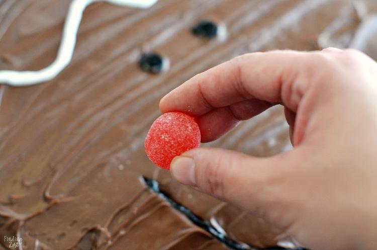 Adding a red gumdrop to a brownie