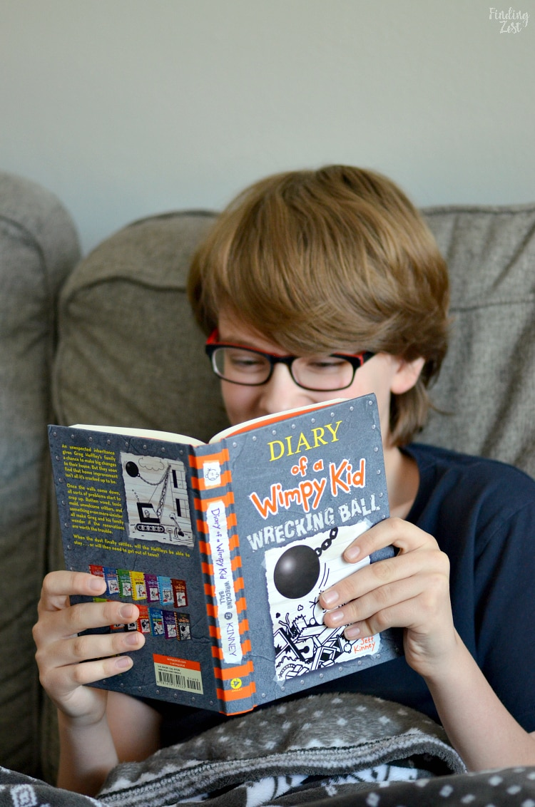 Kid reading Diary of a Wimpy Kid Wrecking Ball Jeff Kinney