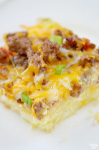 Cut hash brown casserole topped with egg, sausage, cheese and Rotel