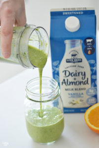 Pouring green smoothie into a glass