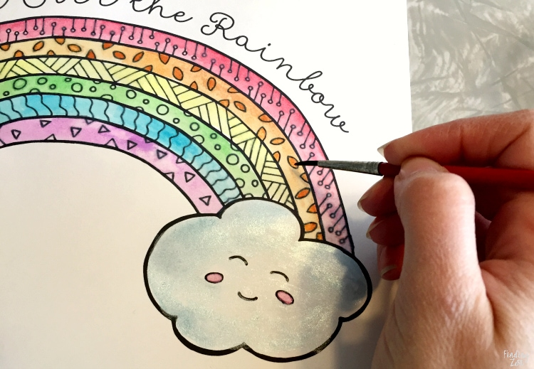 Painting a coloring page with a rainbow and cloud