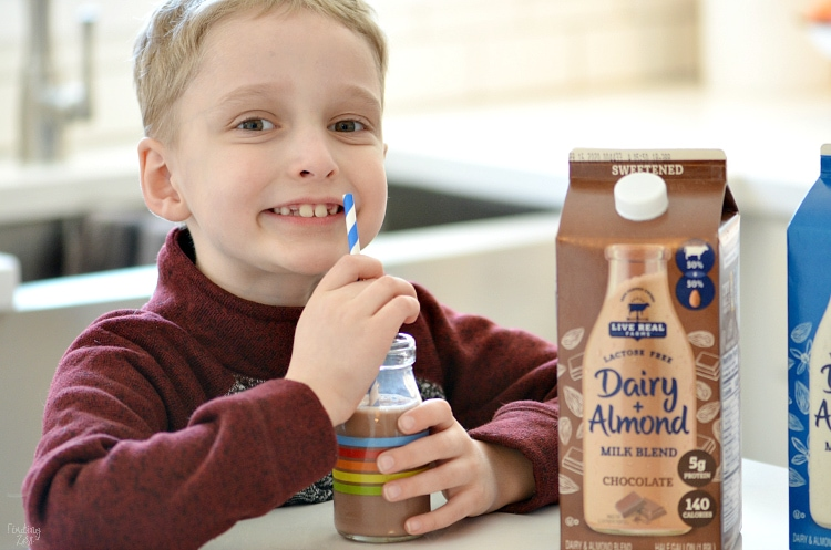 Kid smiling while drinking Live Free Dairy Farms Almond Milk Blend Chocolate