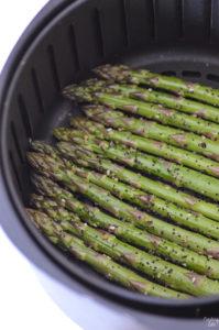 Fresh cut asaparagus in a single layer in a basket style air fryer.