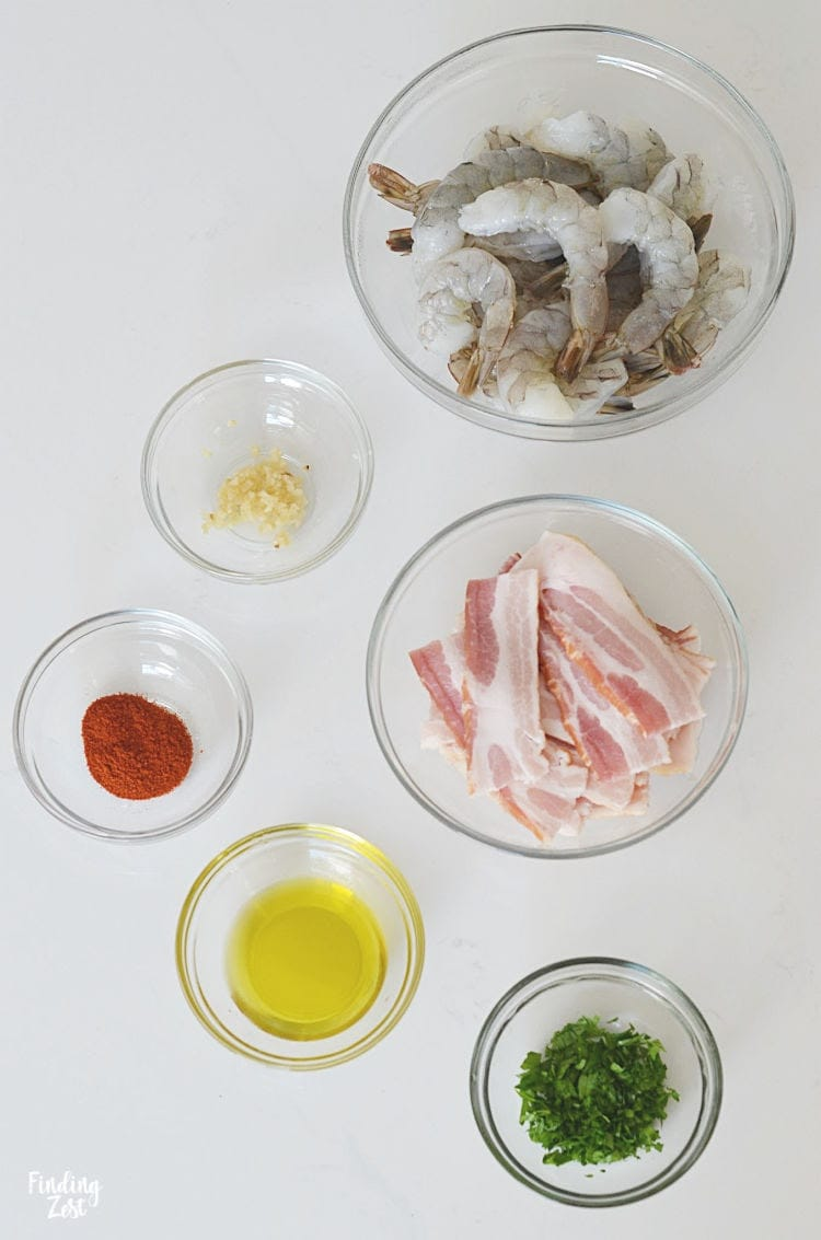 Ingredients for bacon wrapped shrimp including jumbo shrimp, bacon, fresh parsley, garlic paprika and oil