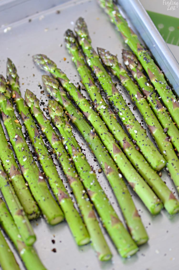 Fresh asparagaus seasoned with everything but the bagel seasoning on a baking tray