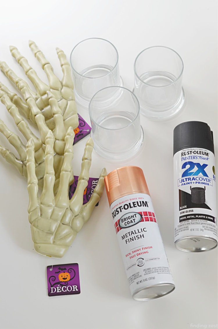 Dollar Tree Halloween Craft Supplies including plastic skeleton hands, glass candle holdersa and spray paint