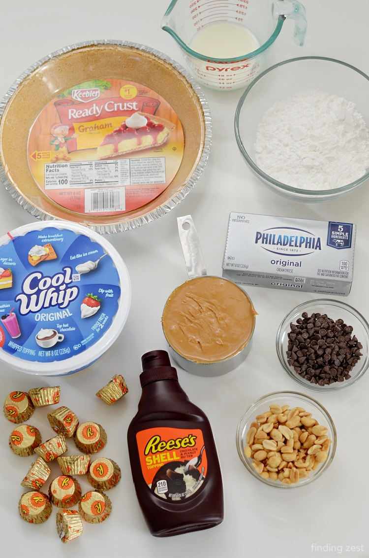 Ingredients needed for a peanut butter pie including creamy peanut butter, cream cheese, milk, cool whip and a graham cracker crust