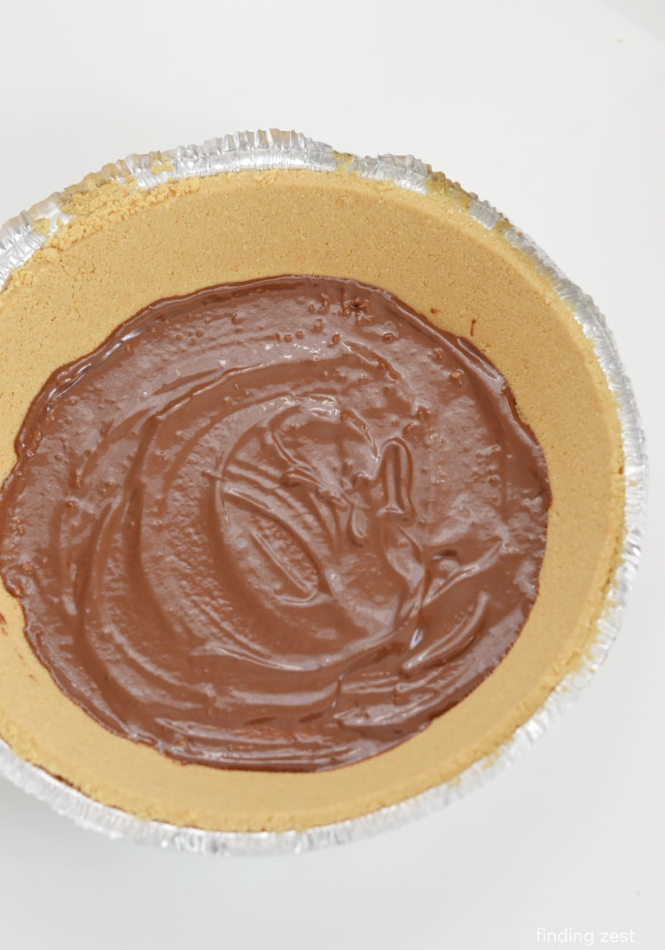 Spreading reeses magic shell over graham cracker crust