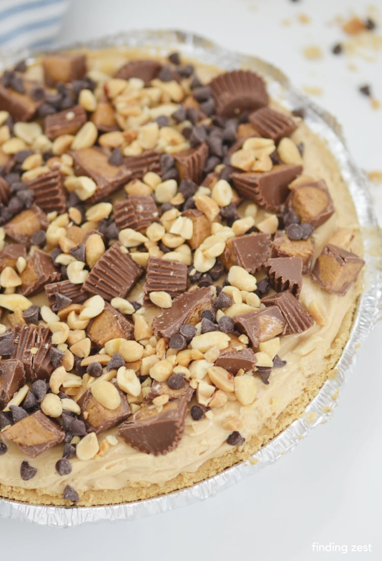 Whole peanut butter pie topped with peanuts, peanut butter cups and mini chocolate chips